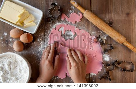 Cooking pink cookies in the shape of animals as a gift for a little girl. Cookie cutters and all the necessary ingredients on a wooden table. Mom lovingly makes cookies (hands in the frame).