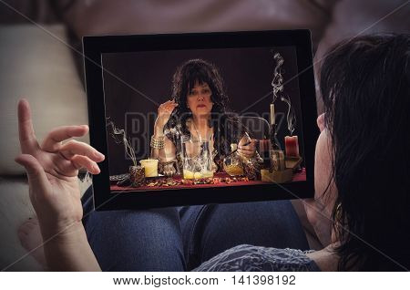 Reclining woman on couch communicates with old psychic by tablet computer. She is doing egg divination online. Black haired fortune teller is reading a shapes of egg whites in touchscreen