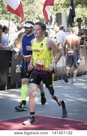 NEW YORK JUL 24 2016: ParaTriathlete from Achilles International crosses the finish line of the NYC Triathlon Race in Central Park, the only International Distance triathlon in the city.