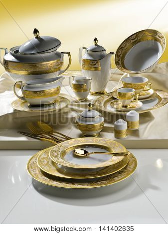 White tableware set with gold trim on the table