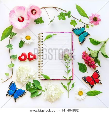Colorful flowers and homemade butterfly and heart shaped cookies floral composition with notebook on light background.  Top view, flat lay.