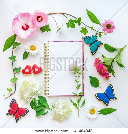 Colorful flowers and homemade butterfly and heart shaped cookies floral composition with notebook on light background. Top view flat lay.