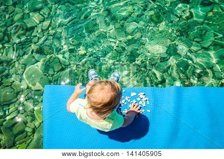 Baby Playing with Stones by the Sea. Top View. Crystal Clear Azure Water of Adriatic Sea Background. Children's Leisure Activity at Vacation Concept. Copy Space.