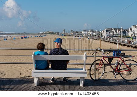Avon-by-th-Sea NJ USA -- Aug 4 2016 Man and woman relaxing on a bench on the boardwalk. Editorial Use Only