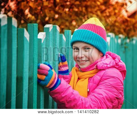 The young smiling girl in the autumn park near the fence.