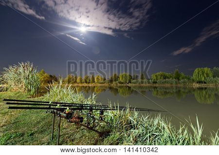 Carp spinning reel angling rods on pod standing. Night Fishing, Carp Rods, Cloudscape Full moon over lake.