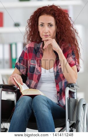 young woman in wheelchair holding book and looking at camera