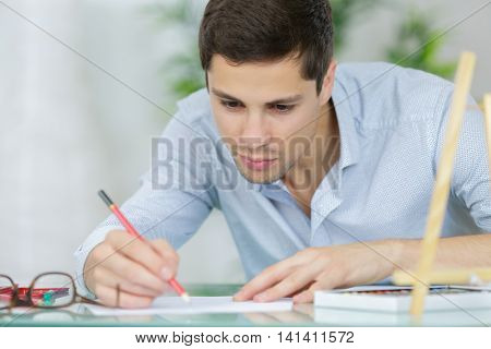 young male architect smiling while sitting by desk with laptop