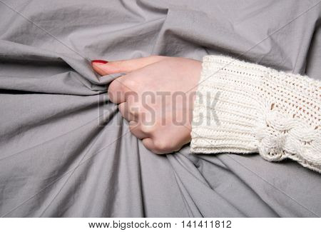 Woman's hand strongly pulling or compressing a gray fabric