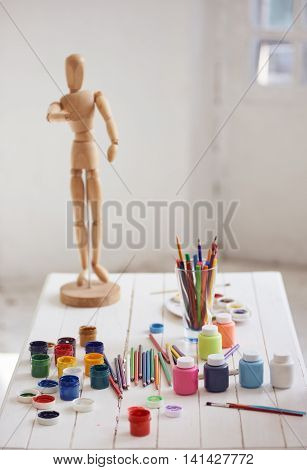 Accessories pencil brushes gouache for drawing and Wooden figure on white table indoor. figure is some blur