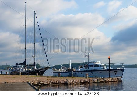 LAPPEENRANTA, FINLAND - AUGUST 09, 2015: A boat and a boat at the pier on the Saimaa lake, august morning. Tourist landmark of the city Lappeenranta, Finland