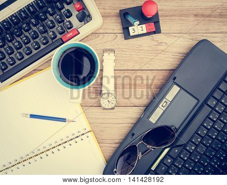 Office desk background. Coffee notepad pencil wristwatch laptop sunglasses and typewriter on vintage wooden desk