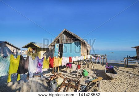 Amazing view colourful T-shirts hanging on a clothesline in front of blue sky and in beautiful beach in Semporna, Malaysia