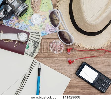 Travel concept with digital camera straw hat sunglasses world map compass passport money wristwatch mobile phone earphones notepad pen and seashell on wooden table