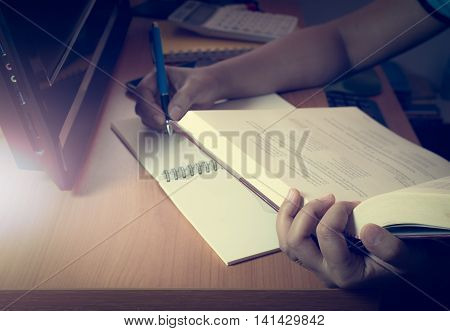 Hands of a girl doing homework on the desk with pc under shinning light