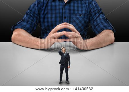 Businessman stands touching his head with his hand in front of cropped portrait of a big man sitting with his clasped fingers. Business staff. Readiness to talk. Boss and employee.