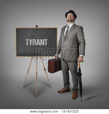 Tyrant text on  blackboard with businessman holding umbrella and suitcase