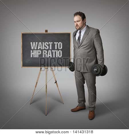 Waist to hip ratio text on blackboard with businesssman holding weights