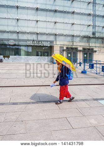 KRAKOW POLAND - JULY 29 2016:. An old woman single female pilgrim going alone to World Youth Day 2016 event in Cracow Poland with a blue backpack and yellow umbrella with US flag