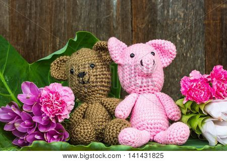 bear doll and pig doll with flowers on wood background