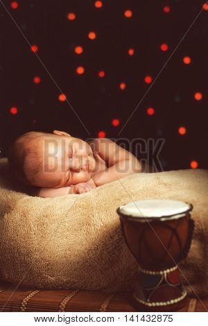 Sleeping newborn baby girl with a drum near to her. Adorable infant portrait.
