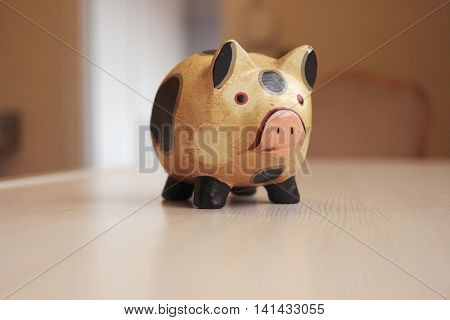 Wooden piggy bank on the table with pink nose