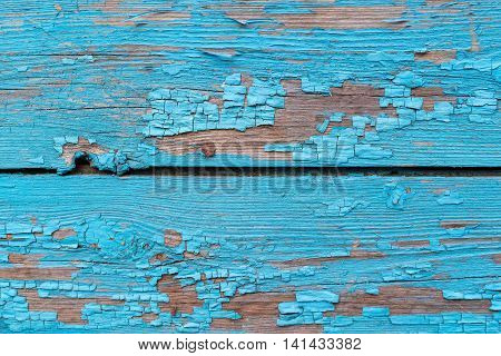 old texture of a peeling of the wooden board painted in the blue color for abstract background