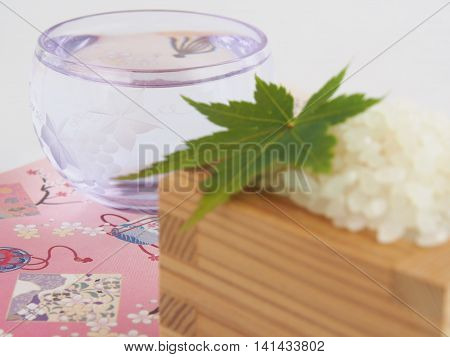 Beautiful sake (rice wine) cup of glass, Blur rice and maple, Japanese paper, on bright white background