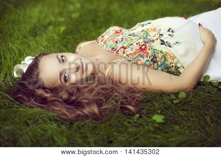 European beautiful pregnant woman in a floral sundress in the summer lies on green grass and looking directly at the camera supports abdomen with hands