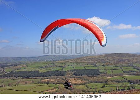 Paraglider flying his wing above Dartmoor in Devon