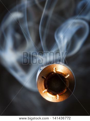 Hollow point bullet with copper plating and smoke on a black background