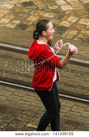 Lviv Ukraine - May 2 2016: Celebration pouring water on Monday after Easter by the town hall. Happy girl pouring water on each other.