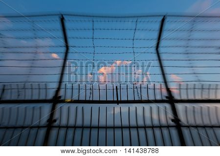 Barbed wire fence silhouettes against cloudy dark blue sky at sunset with blur effect