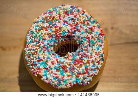 Donut with sprinkles , on wooden background