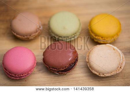 Macrons on wood , sweets for dessert