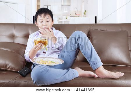 Overweight little boy enjoy cheeseburger while sitting on the couch and suck his finger at home