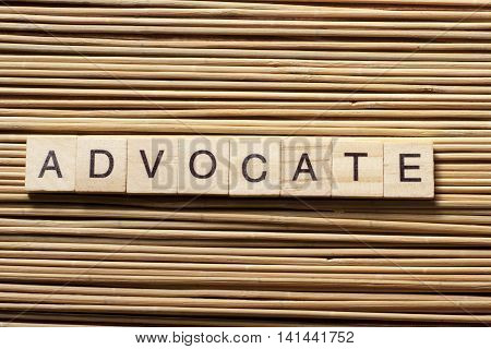 Advocate word written on wood abc block at wooden background.