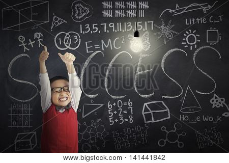 Cheerful little boy showing OK sign with bright lightbulb and doodles on the blackboard shot in the classroom