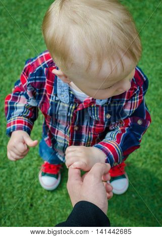 Stylish hipster toddler in sneakers jeans and shirt standing and holding father's finger. A parent holds the hands of a little baby boy. Support concept.