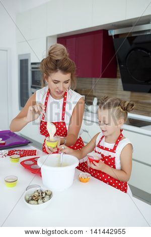 A young woman and her five year old daughter together prepare cakes for the festive table on the big kitchen with the wall cabinets,blonde hair mother and daughter collected in her hair,mother and daughter are wearing red aprons with white polka dots