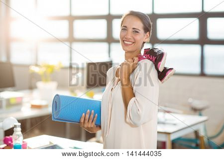Female business executive holding exercise mat and shoes in office