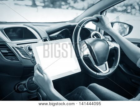 Using a tablet computer driving a modern car.