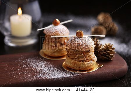 Praline hazelnut choux on wooden tray with pine for Christmas