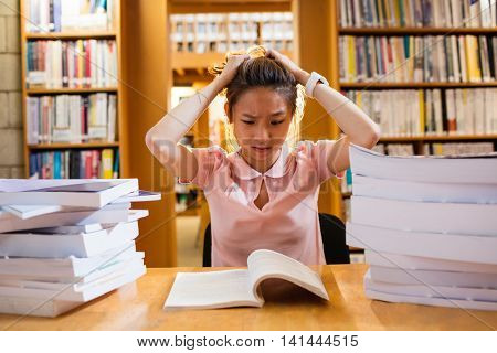 Tensed young woman studying in library at college