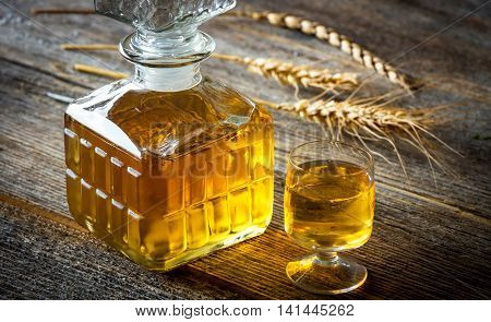 Glasse Of Brandy Or Cognac And Bottle On  Wooden Table.