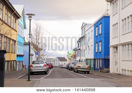 Reykjavik Iceland - November 11 2014: Colorful builing along small road in capital city. Seeing white mountain of winter at the end of street