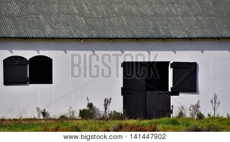 Close up of white Horse stable with black door