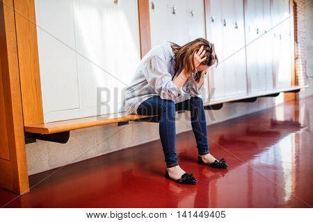 Tensed woman sitting in locker room at college