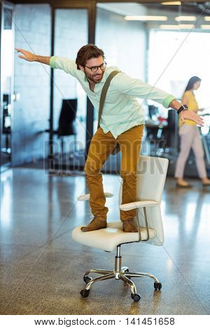 Male business executive standing on chair in office