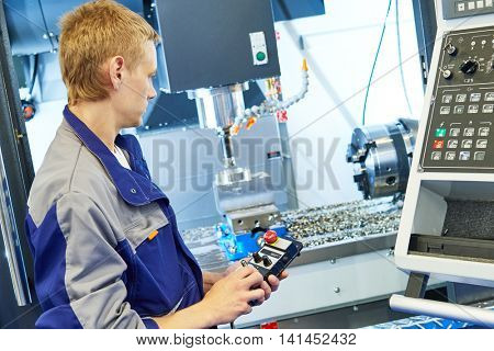 metal machining industry. Worker operating cnc milling machine